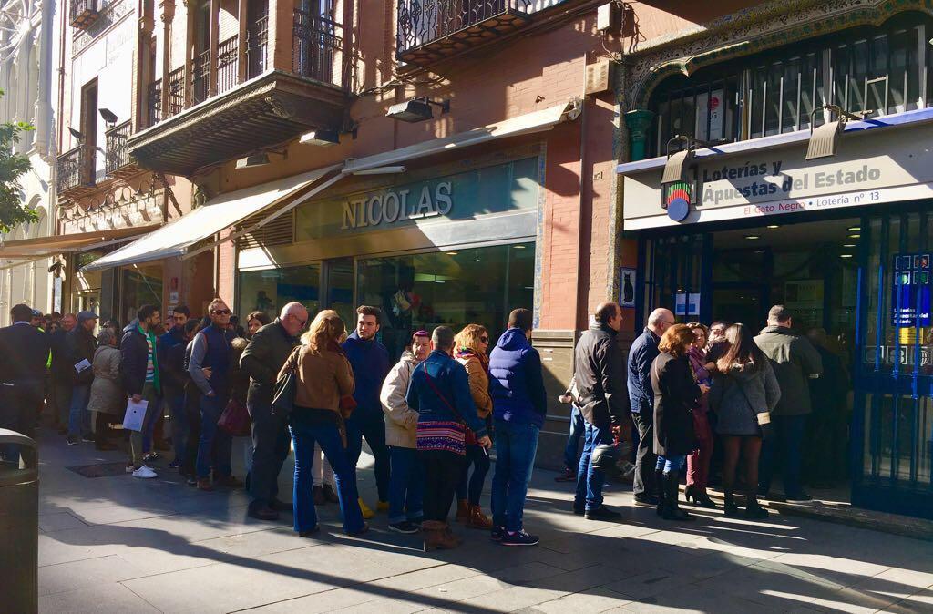 Sevillanos haciendo cola frente a una administración de Lotería.